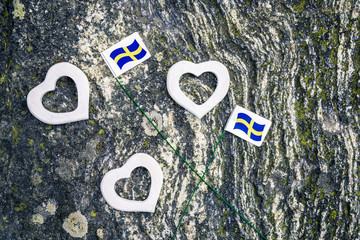 Swedish flags and white hearts on mossy rock background
