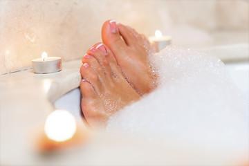 Woman's feet in bath foam . Relaxation in hotel or spa.