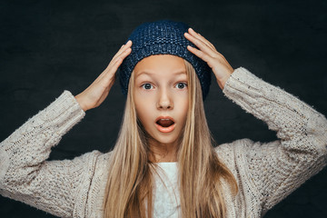 Portrait of a surprised teen girl with blonde hair wearing a winter hat and sweater