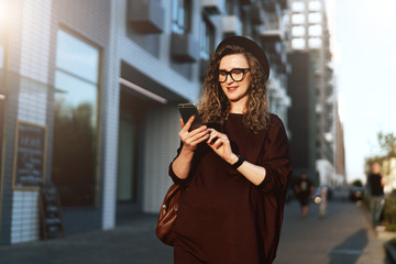 Young curly hipster woman in trendy glasses and hat walks on city street and uses smartphone. Social media,lifestyle.