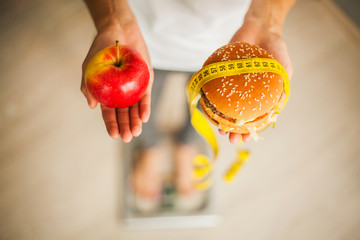 Diet. Woman Measuring Body Weight On Weighing Scale Holding Burger and red apple. Sweets Are Unhealthy Junk Food. Weight Loss. Obesity. Top View