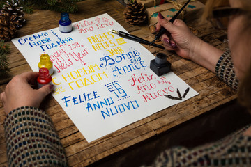 Woman writing happy new year in different languages