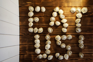 Eat me. Letters from dumplings on dark and light boards. Country style. Russian dish