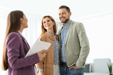 Female real estate agent working with couple in room