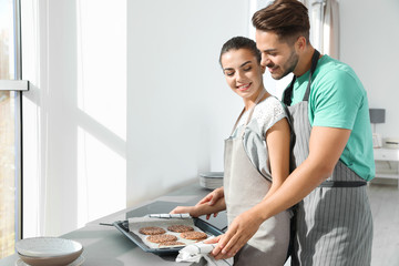 Young couple with oven sheet of homemade cookies in kitchen, space for text