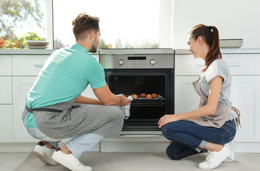 Young couple baking croissants in oven at home