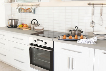 Stylish kitchen interior with modern oven and set of cooking utensils