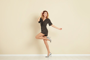 Young woman with beautiful long legs in stylish outfit near color wall