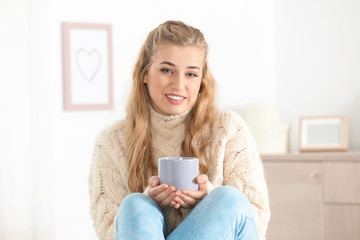 Attractive young woman in cozy warm sweater with cup of hot drink at home