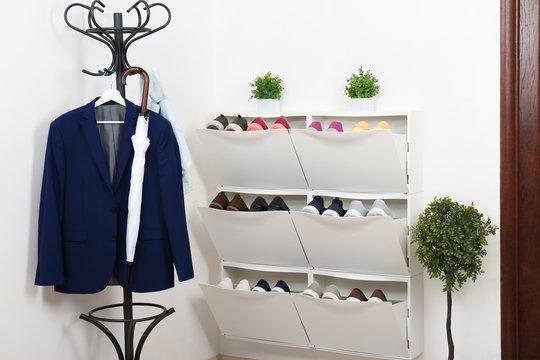 Shoe cabinet with footwear in room. Storage ideas