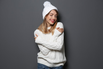 Wall Mural - Beautiful young woman in warm sweater with hat on dark background