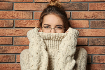 Beautiful young woman in warm sweater near brick wall