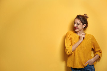 Beautiful young woman in warm sweater on color background. Space for text Fototapete