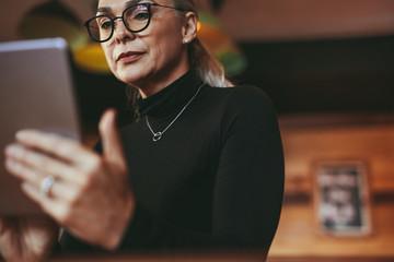 Senior woman at cafe using digital tablet
