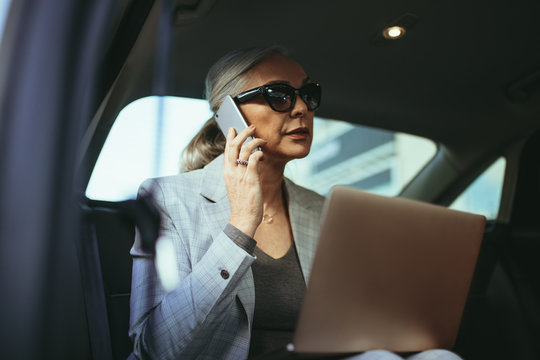 Female entrepreneur working while traveling in a car