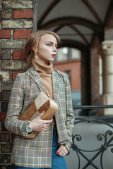 Outdoor portrait of young beautiful lady wearing stylish checkered blazer, turtleneck, jeans, silvery analog wrist watch, with suede brown, beige bag posing in street of european city