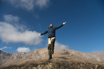 Hipster traveler with a beard with arms spread in different directions levitates against the background of mountain cliffs and a blue sky with clouds. Freedom to travel