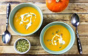 Roasted pumpkin and carrot soup with cream and pumpkin seeds on wooden background. Top view. Copy space