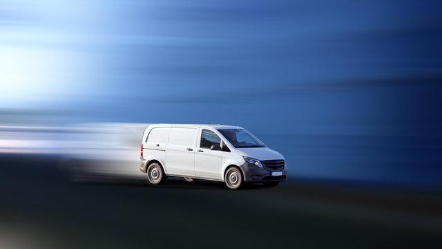 Servicefahrzeug unterwegs in dynamischer Fahrt vor blauem Hintergrund mit Bewegungsunschärfe