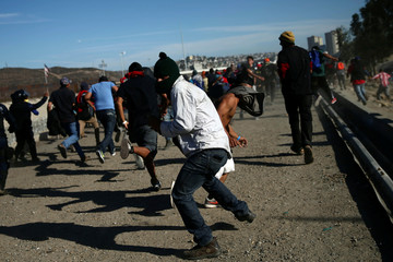 Migrants, part of a caravan of thousands traveling from Central America en route to the United States, run from tear gas released by U.S. border patrol near the fence between Mexico and the United States in Tijuana