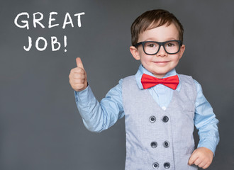 Cute little boy giving thumbs up saying Great Job