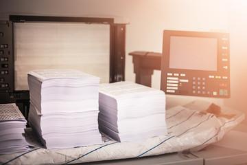 Pile of printed papers on industrial printer