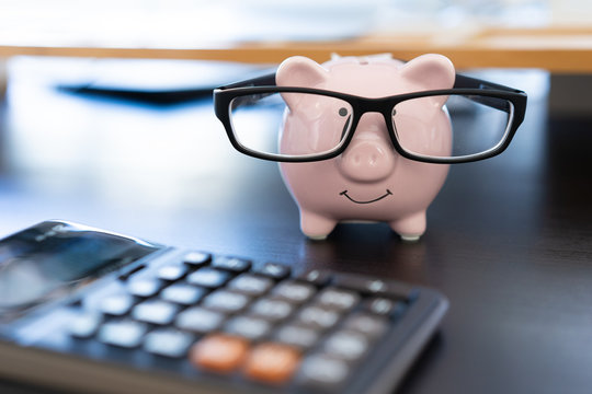 piggybank And Calculator On Desk business document calculator counting money