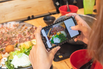 woman taking photo of sukiyaki shabu shabu with mobile smartphone