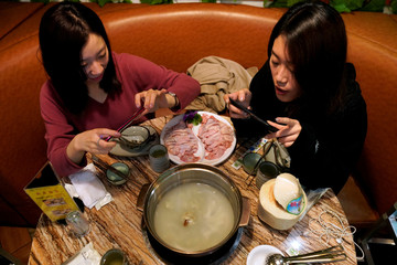 Customers take pictures of a durian hotpot at Coconut Chicken Hotpot Store in Shanghai