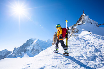 Fototapete - A skier is standing on the mountain top.