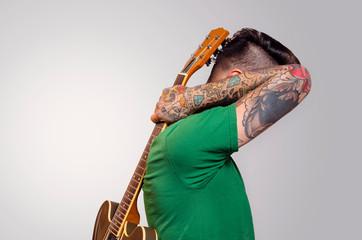 Artistic portrait Tattooed rocker male, holding guitar on his back