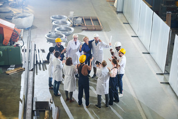Group of happy  factory workers applauding during meeting with management in large industrial workshop, copy space