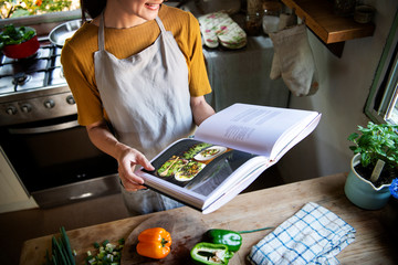 Canvas Prints Cooking Happy woman reading a cookbook in the kitchen