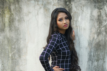 Portrait of a young and beautiful Indian Bengali lady in black western short dress posing in front of a roughly textured white wall. Indian lifestyle and fashion portrait
