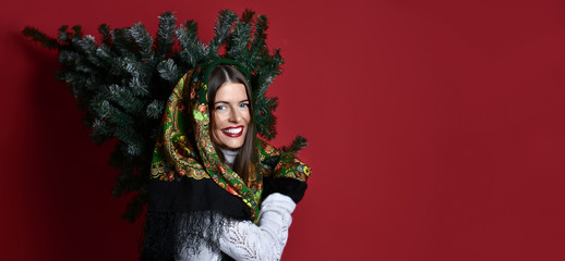 Happy Russian style woman with scarf hold Christmas  tree on her shoulders happy laughing