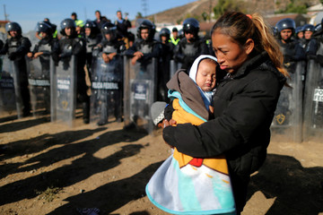 Rosa Villa and her five-month-old son Esteban from Honduras, part of a caravan of thousands traveling from Central America en route to the United States, are pushed back from the border wall between the U.S and Mexico by Mexican police in Tijuana