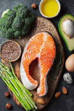 A set of healthy food for keto diet on a dark background. Fresh raw salmon steak with flax seeds, broccoli, avocado, chicken and quail eggs, nuts and asparagus on a wooden Board. Top view