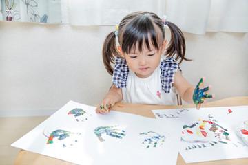 手の平に絵具を塗り遊ぶ幼い女の子。育児、子育て、教育、知育イメージ