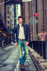 European businessman traveling in New York. Wearing black leather jacket, white undershirt, blue jeans, brown boot shoes, a young guy with beard walking on narrow wet street after raining,
