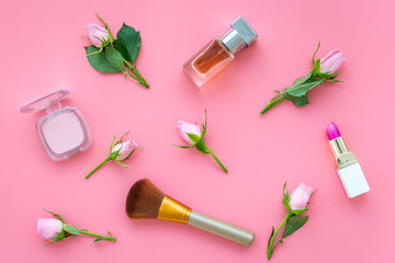 Makeup products for young girls. Composition with cosmetics with rose tones. Lipstick, bulk, eyeshadow, perfume, brushes and rose flowers on pink background top view