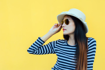 Sunny lifestyle fashion portrait of young stylish hipster woman beside building against yellow background, wearing trendy outfit, hat, travel concept.