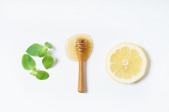 lemon, honey and mint leaves on white background