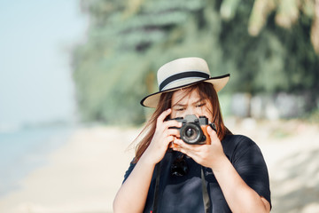 travel  background portrait young woman photographer holding camera for taking photo on beach