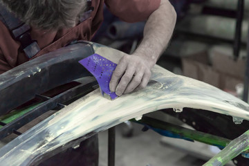 A man prepares a car body element for painting after an accident with the help of abrasive paper in a car repair shop. Recovery bumper after a collision.