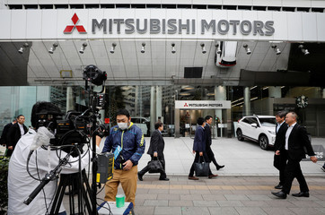 A TV crew and passersby are seen in front of Mitsubishi Motors Corp's headquarters in Tokyo