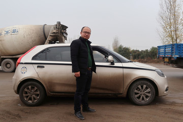 Cao Jun poses for a photo near his six-year-old MG3 car at Lushan county