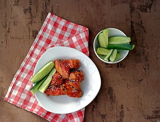 Baked chicken wings in a barbecue sauce, sprinkled with sesame. Served with sliced fresh cucumbers.