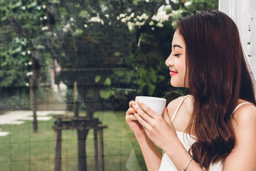 Beautiful young woman relaxing holding a cup of coffee in cafe