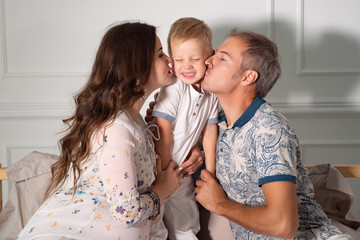 Cheerful expectant couple playing with son in living room at home.