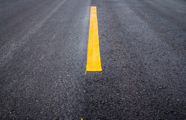 Asphalt road surface with yellow line